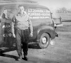 Older photo of an IT Landes plumbing and heating truck and employee